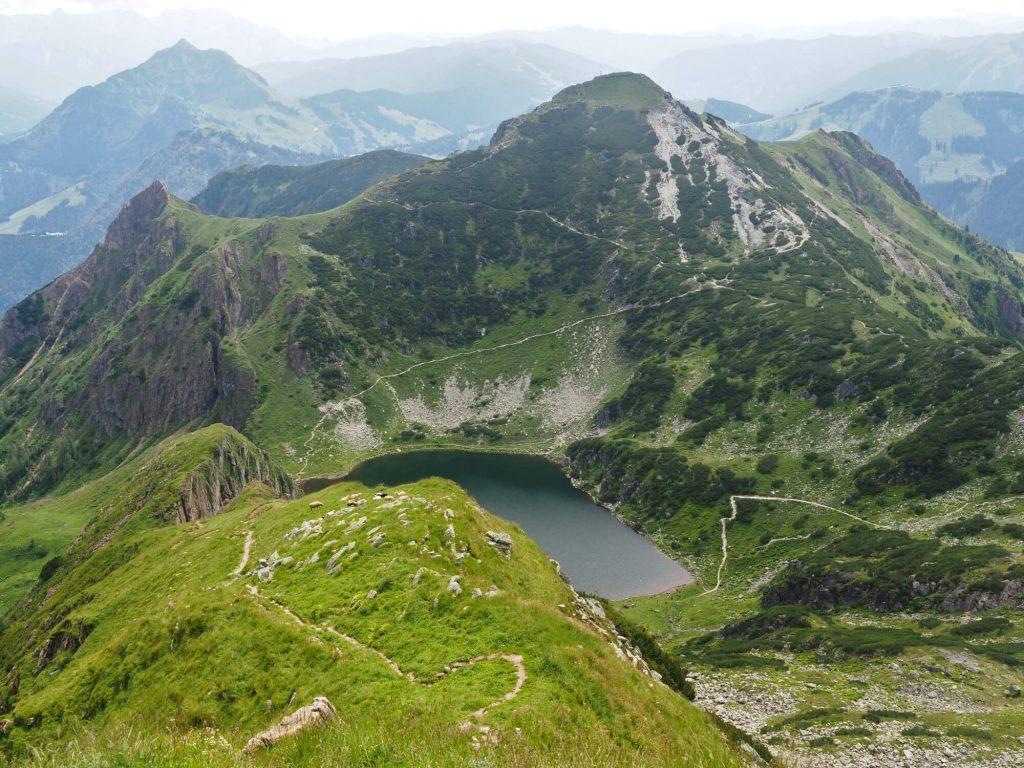 De steile route over een smalle bergkam naar de Wildseeloder met uitzicht op het bergmeer de Wildsee en de bergtop Henne