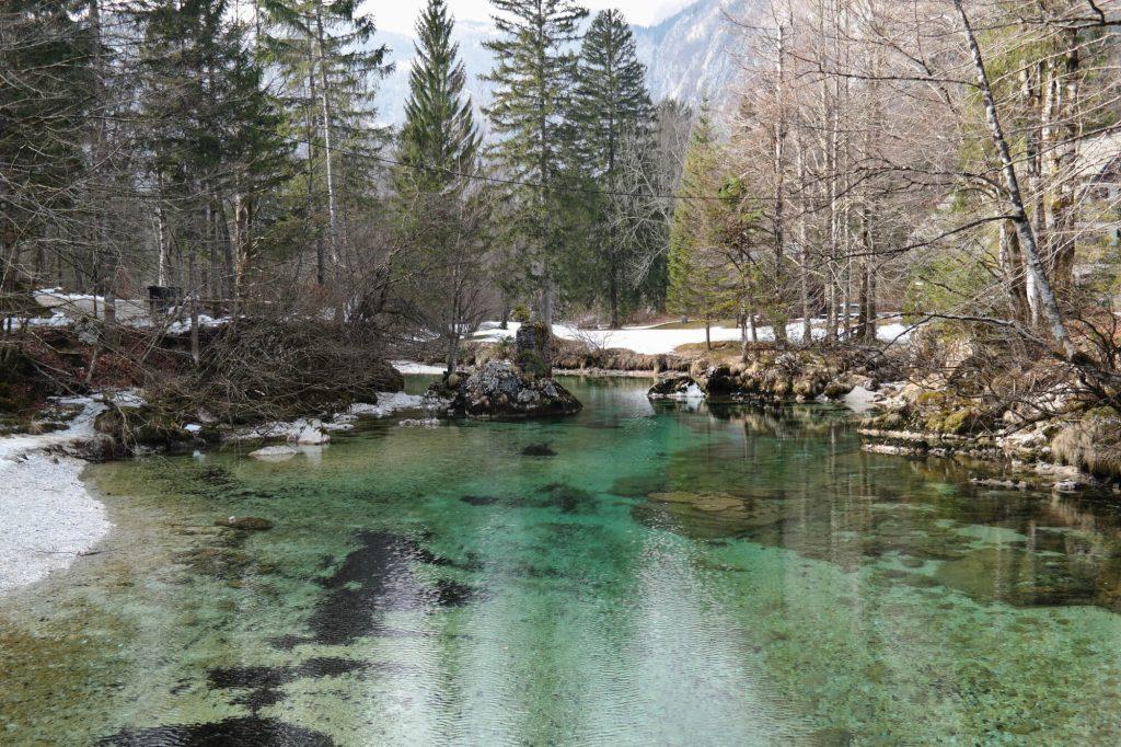 Blauwgroene rivier mets sneeuw bij het meer van Bohinj
